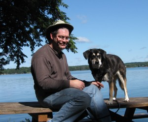 Mixed breed dog and man on picnic table.
