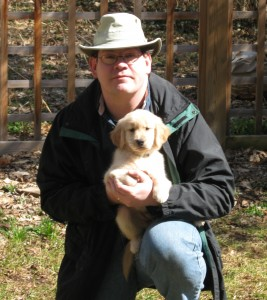 Man Holding Golden Retriever Puppy