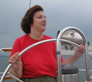 Woman at wheel of sailboat on Lake Ontario