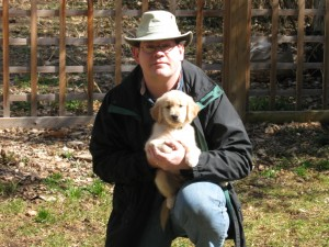 Man in Hat Holding Golden Retriever Puppy