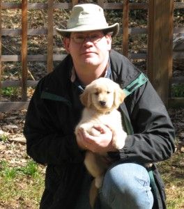 Man in hat holding a golden retriever puppy.
