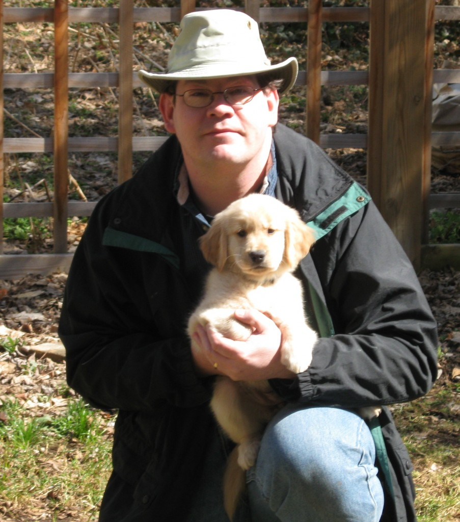 Man in hat holding a golden retriever puppy.