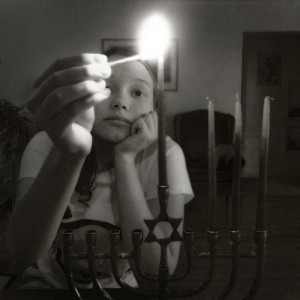 A girl is lighting the menorah on the third day.