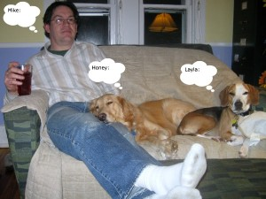 Mike and two dogs share a love seat.