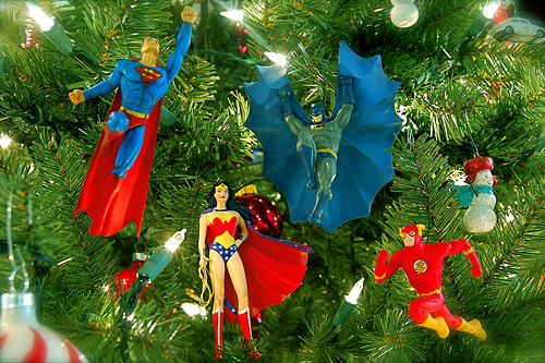 Superman, Batman, Wonder Woman and Flash guard a Christmas tree.