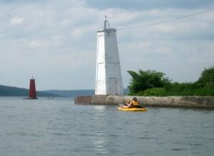 Honey the golden retriever passes the Ithaca light house in a kayak.