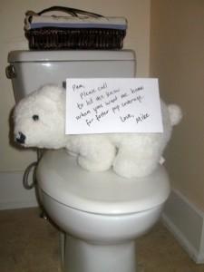 A stuffed polar bear sits on the toilet seat.