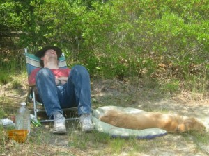 Honey the Golden Retriever and Mike nap on the beach.