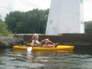 Kayaker with a dog passing a lighthouse in Cayuga Lake.