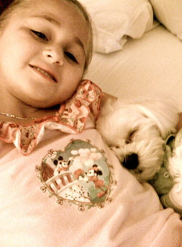 A little girl sleeps with her dog.