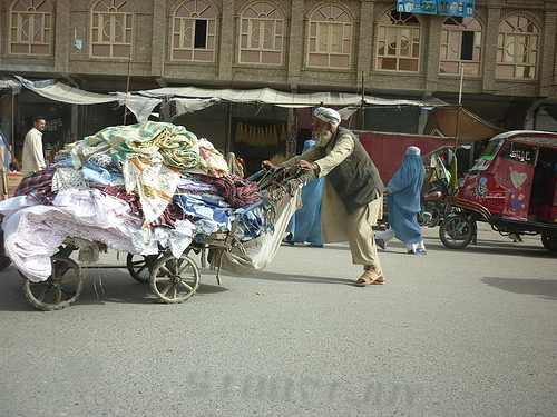 A man pushes a cart of fabric in Herat, Afghanistan.