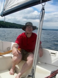 Mike is the captain at the tiller of a sailboat.