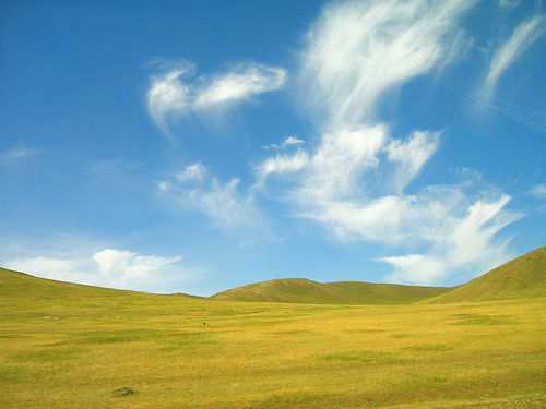 Mongolia's most prevalent features are hills, grass, and clouds.
