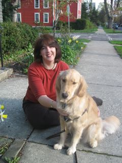 Pamela poses beside Honey the Golden Retriever.