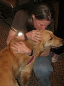 Honey the golden retriever cuddles with Leslie at BlogPaws.