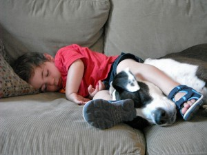 Child and dog zonked on couch.