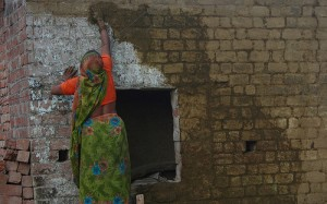 An Indian woman paints her house with dung.