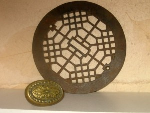 Brass door knob and metal grate architectural items.