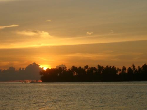 A Guna Yala island in the Caribbean sea at sunset.