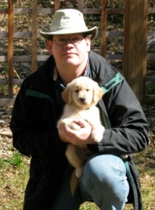 Honey the golden retriever puppy in Mike's arms.