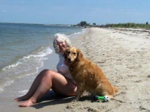 Honey the golden retriever an Pam on the beach.