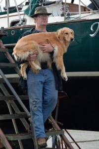 Honey the golden retriever is resigned to being carried down the boat steps.