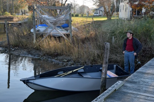 Mike with folding dinghy in water.