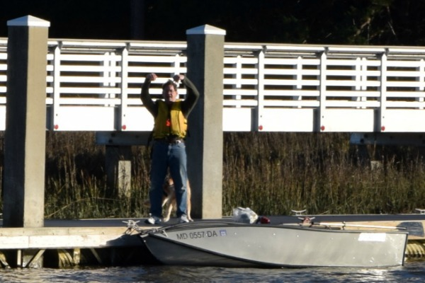 Mike raises his hands triumphantly after rowing to shore at Steamboat Landing.