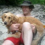 Honey the Golden Retriever sits in MIke's lap at the side of the creek.