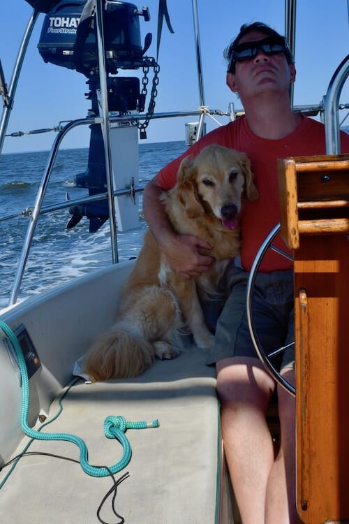 Honey the boat dog finds the shade with Mike on the helm.