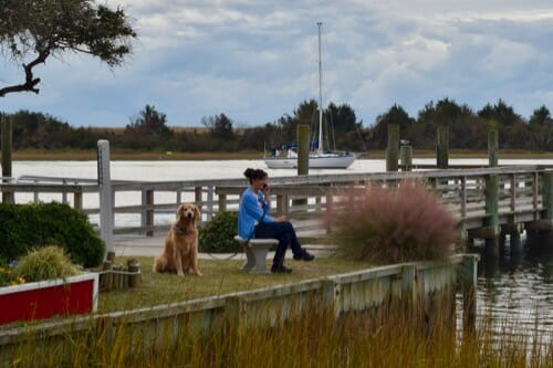 Woman talking on phone at dock next to golden retriever.